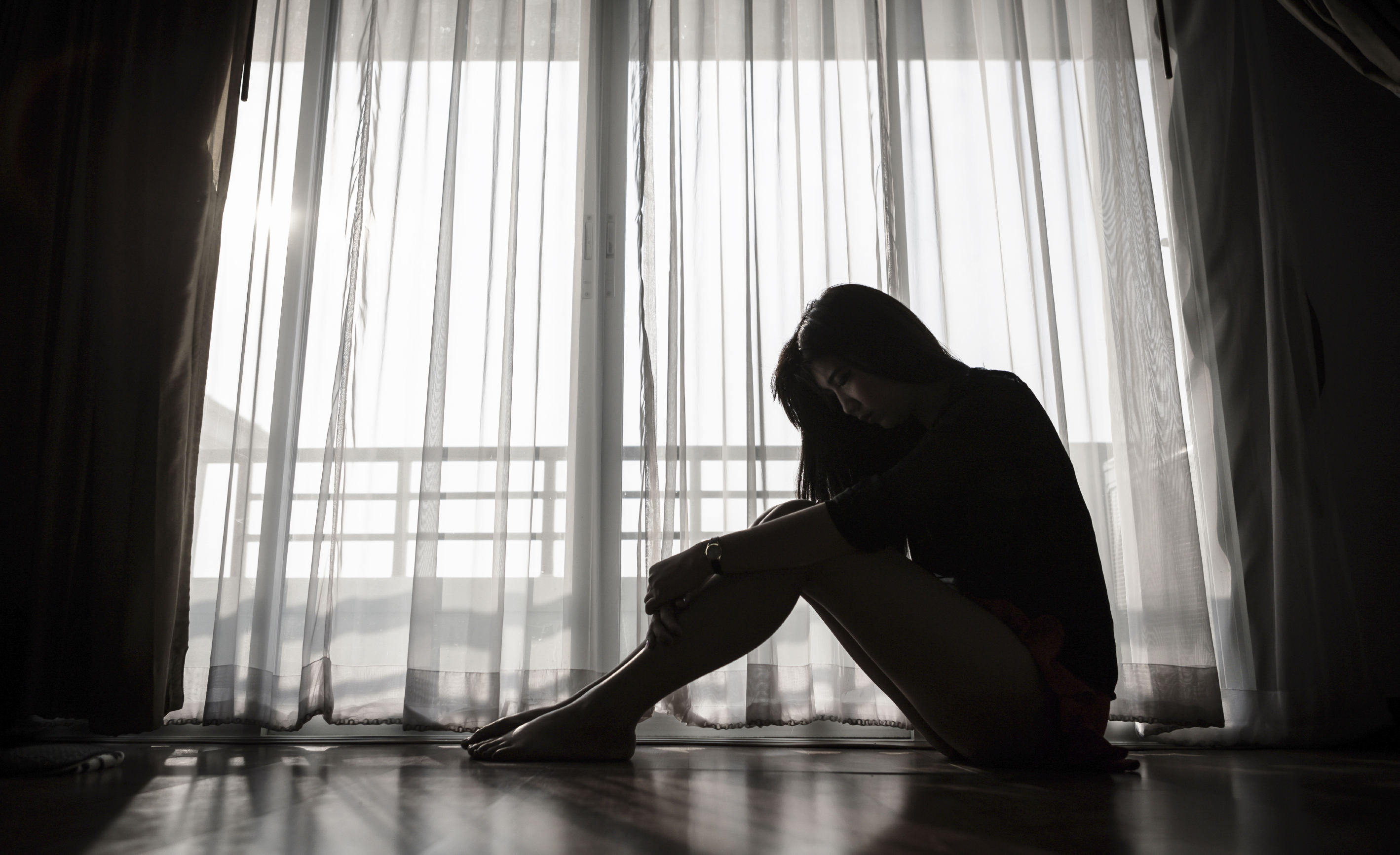 Woman in Dark Room Clasping Legs on Floor