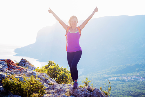 Woman in Cheering Pose on Mountain Top