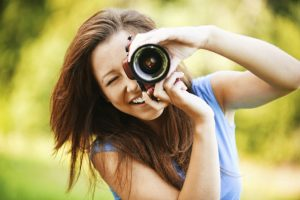 Smiling Woman Taking a Photo with a Camera