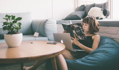Young Girl Reading Book w/ Laptop & iPhone Nearby
