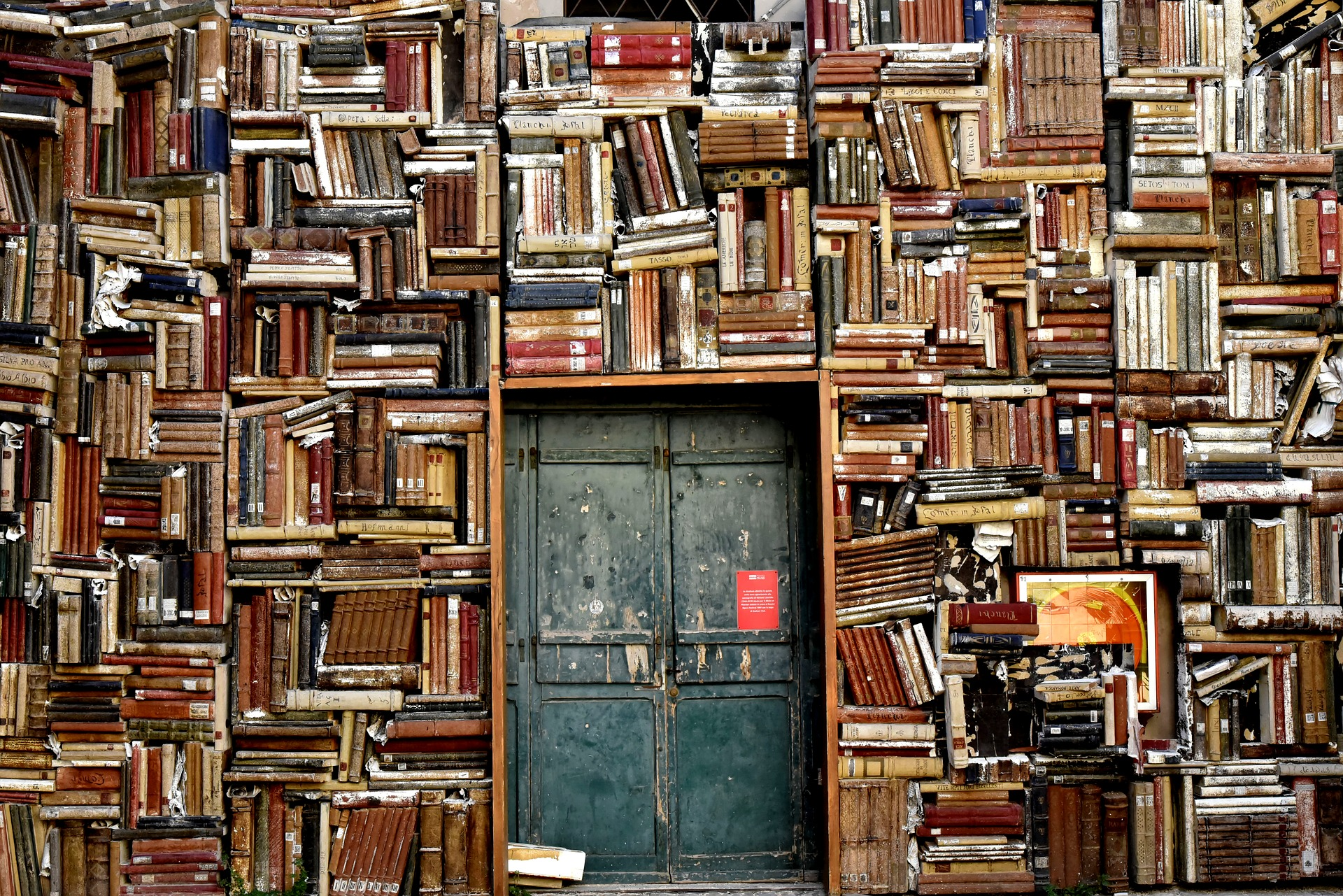 Books Arranged Haphazardly On An Entire Wall and a Green Door