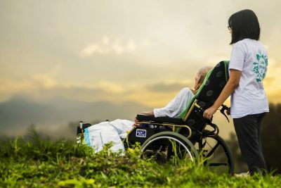 Person Pushing Aged Person in Wheelchair in a Field