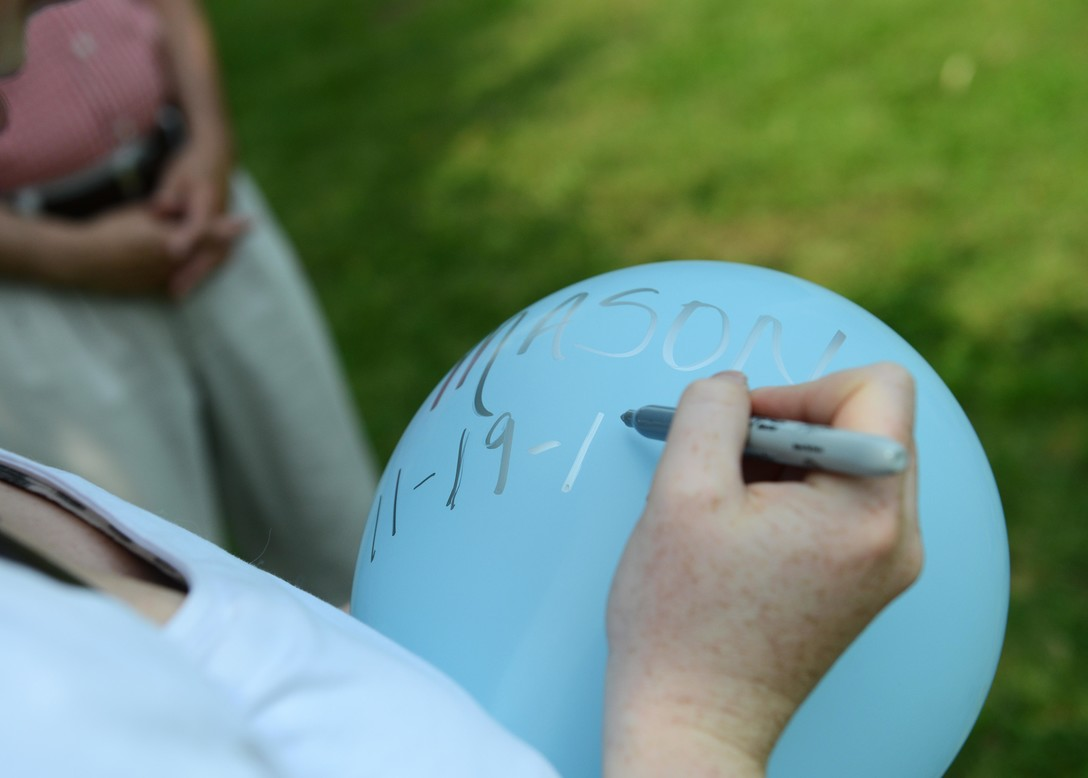 Brooke El-Attrache writes the name of her stillborn nephew, Mason, and the date he passed away, on a balloon