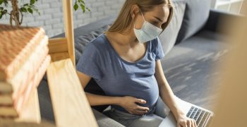 pregnant woman wearing a mask working
