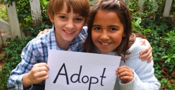 two kids holding adopt sign