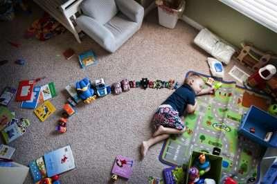 little boy on ground with trucks